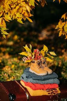 Ciepły sweter na walizce w stylu vintage i stare buty z liśćmi w środku