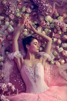 Ciepły wieczór. widok z góry piękna młoda kobieta w różowej spódniczce baletowej otoczonej kwiatami. wiosenny nastrój i delikatność w koralowym świetle. koncepcja wiosny, kwitnienia i przebudzenia przyrody.