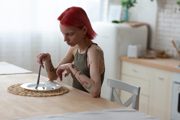 Cierpi na anoreksję. rudowłosa kobieta z zaburzeniami odżywiania, niejedząca nic, cierpiąca na anoreksję