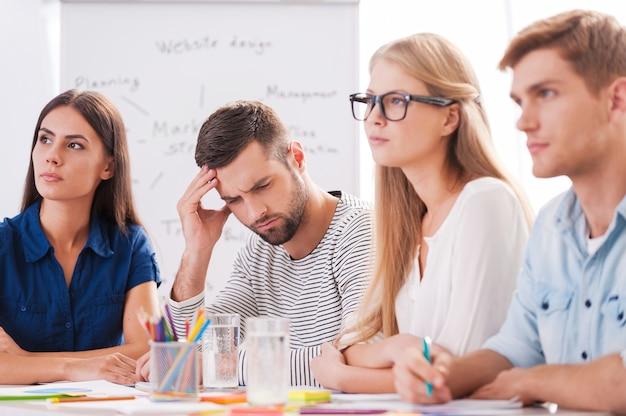 Cierpi na okropny ból głowy. przygnębiony młody człowiek dotyka głowy ręką, siedząc przy stole razem ze swoimi kolegami