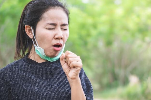 Cierpiąca kobieta azji kaszel na zewnątrz