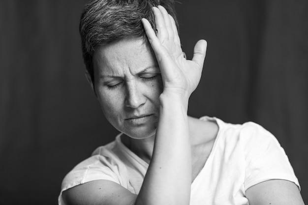 Cierpienie na twarzy dorosłej kobiety o krótkich siwych włosach. czarno-biały portret.