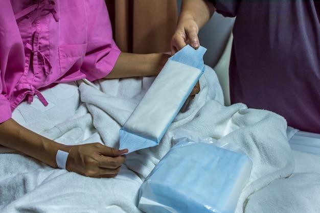 Cierpliwa azjatykcia kobieta z adhezyjnym tynkiem na ręce używać higieniczną pieluchę dla miesiączki