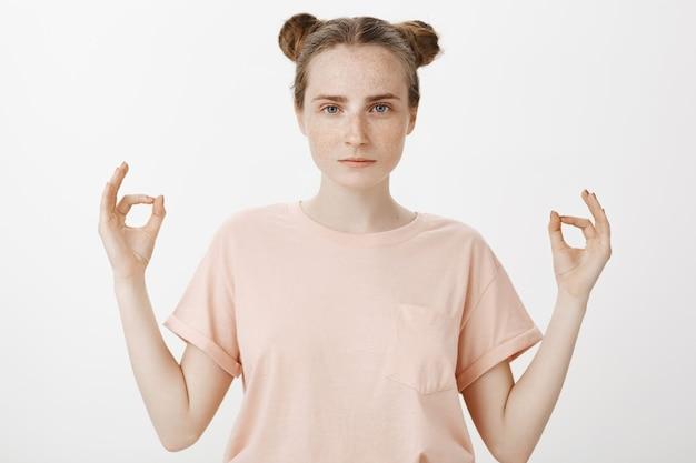Cierpliwa nastolatka pozuje na białej ścianie
