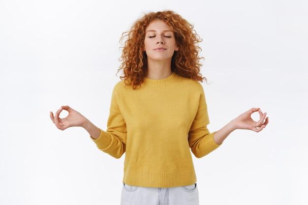Cierpliwa, zrelaksowana i zdeterminowana młoda atrakcyjna kobieta o rudych kręconych włosach, zamkniętych oczach i uśmiechnięta, oddycha spokojnie i zrelaksowana podczas medytacji, rozkłada ręce na boki w nirwanie, joga