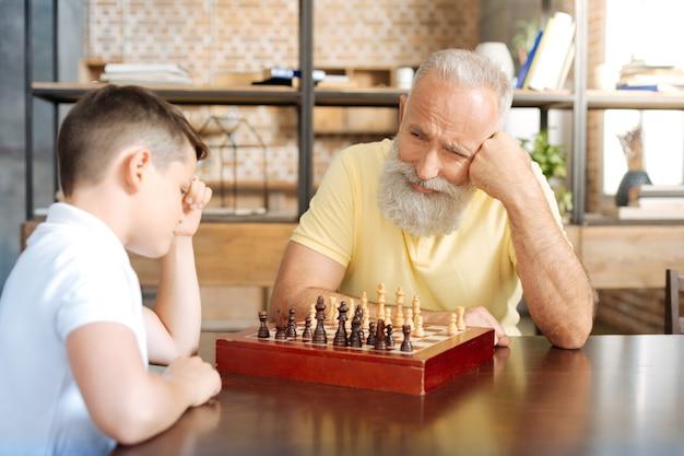 Cierpliwie czekając. przyjemny starszy mężczyzna grający w szachy ze swoim uroczym wnukiem przed nastolatkiem i patrząc na niego z uśmiechem, czekając na następny ruch