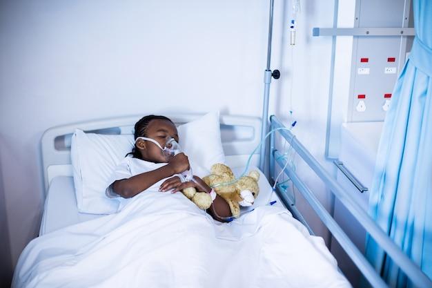Cierpliwy dosypianie z misiem na łóżku przy szpitalem