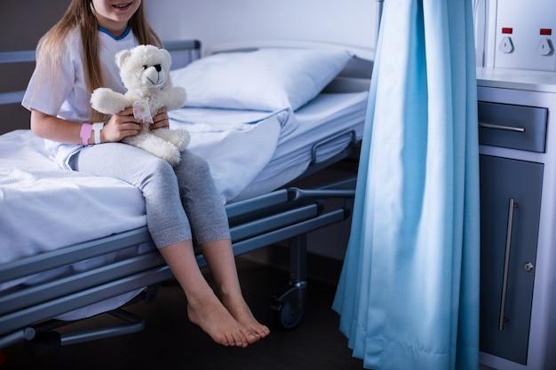 Cierpliwy obsiadanie z misiem na łóżku szpitalnym