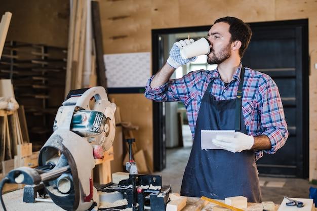 Cieśla bierze kawową przerwę trzyma notatnika przed kurendą zobaczył przy jego warsztatem