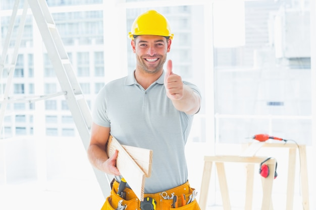 Cieśla gestykuluje aprobaty przy budową