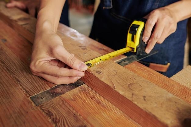 Cieśla mierzący drewnianą deskę