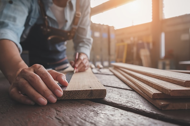 Cieśla praca ze sprzętem na drewnianym stole w sklepie stolarskim.