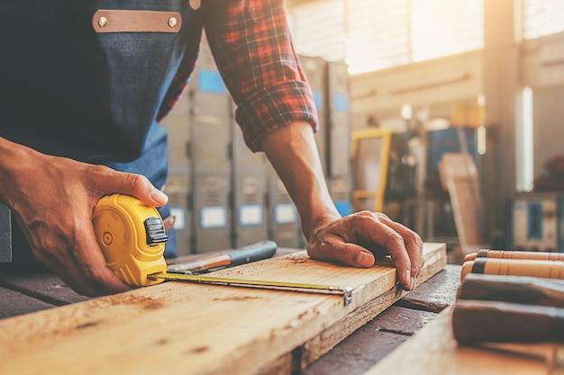 Cieśla praca ze sprzętem na drewnianym stole w sklepie stolarskim
