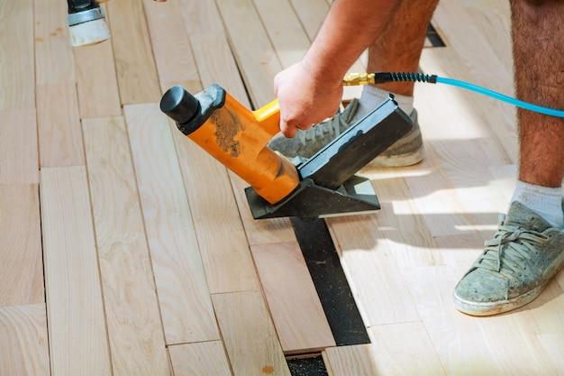 Cieśla pracownik instaluje drewnianą parkiet deskę