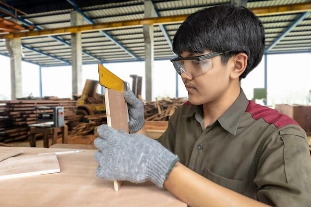 Cieśla pracuje na maszynach do obróbki drewna w sklepie stolarskim. wykwalifikowany stolarz wycina kawałek drewna w swoim warsztacie stolarki.