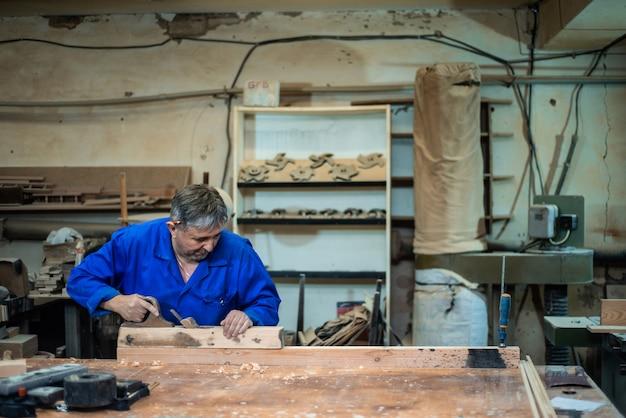 Cieśla pracuje w warsztacie, pracownik planuje drzewo strugarką