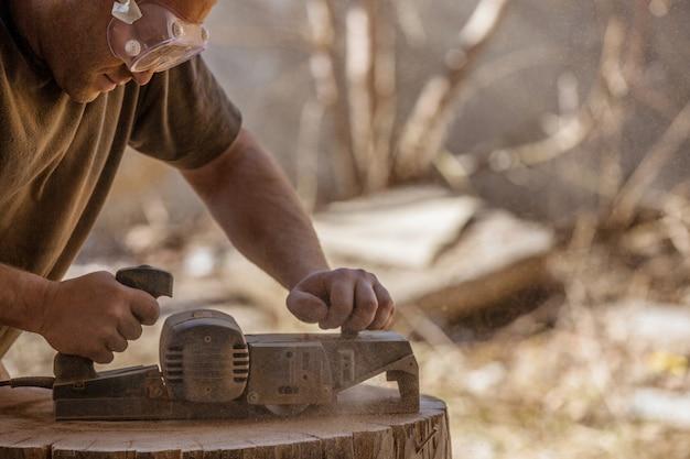 Cieśla pracuje z elektryczną strugarką na drewnianym pniu na wolnym powietrzu, w okularach.