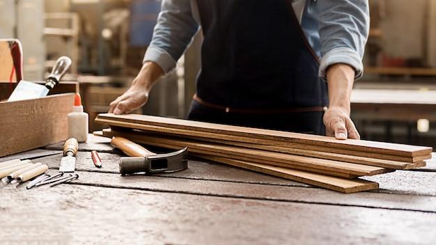 Cieśla pracuje z wyposażeniem na drewnianym stole w ciesielka sklepie. kobieta pracuje w sklepie stolarskim.