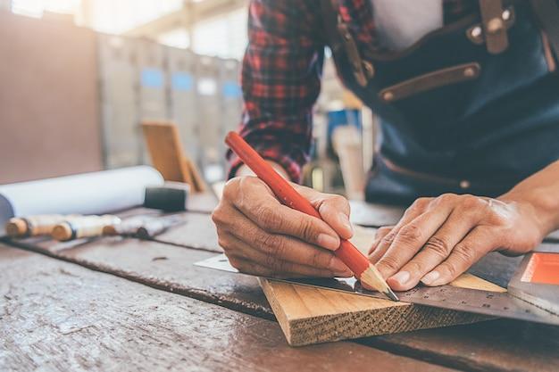 Cieśla pracuje z wyposażeniem na drewnianym stole w ciesielka sklepie.