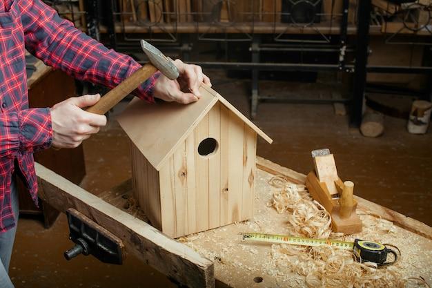 Cieśla robi drewnianego gniazdowego pudełko