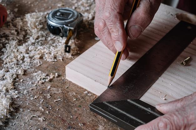 Cieśla robi pomiarom na stole z ołówkiem i metalowym kwadratem
