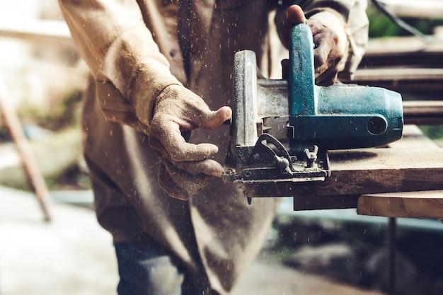 Cieśla używa kółkową saw dla ciąć drewniane deski