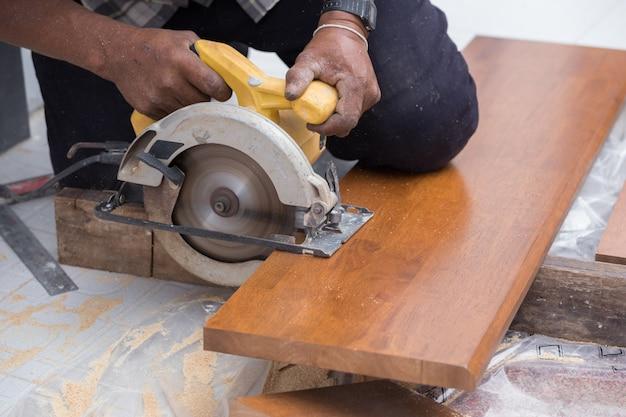 Cieśla używaj piły elektrycznej do piłowania drewna