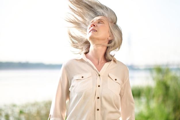 Ciesz się chwilą. siwowłosa energiczna dorosła kobieta z opadającymi powiekami w jasnym garniturze z wiatrem we włosach na zewnątrz w letni dzień