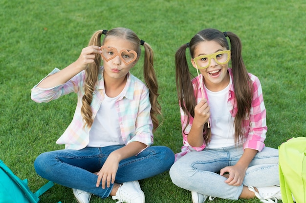 Ciesz się czasem zabawy. powrót do szkoły. literatura dla dziewcząt. odrabiajcie razem pracę domową. znaleźć coś ciekawego w książce. robienie notatek. spędzaj wolny czas z imprezowymi okularami. małe dzieciak przyjaciele relaksują się na trawie.