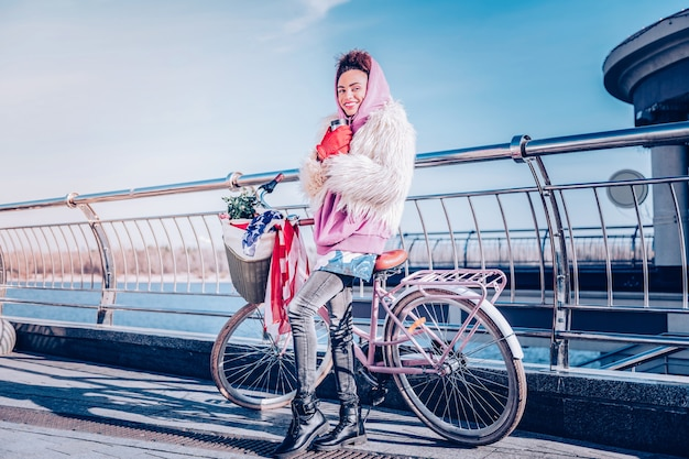 Ciesz się dniem. zachwycona dziewczyna wyrażająca pozytywne nastawienie stojąc obok swojego roweru