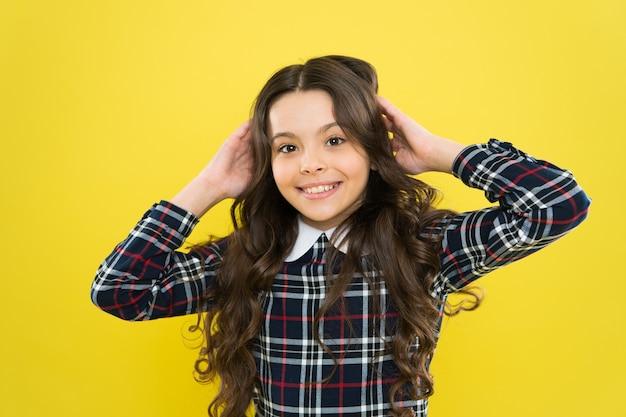 Ciesz się idealnymi włosami. mała dziewczynka ładna fryzura. dziecko długie kręcone włosy. stylowy mundurek szczęśliwy uczennica. koncepcja szczęśliwego dzieciństwa. szczęśliwy uśmiechający się wesoły portret dziecka. emocje wyrażania emocji.