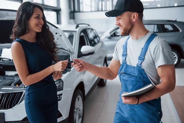 Ciesz się jazdą. kobieta w salonie samochodowym z pracownikiem w niebieskim mundurze, odbierając naprawiony samochód