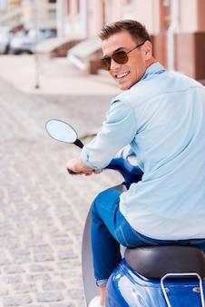 Ciesz się jazdą na skuterze. widok z tyłu wesoły młody człowiek w okularach przeciwsłonecznych jeżdżący skuterem wzdłuż ulicy i patrzący przez ramię