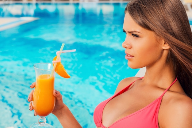 Ciesz się latem przy basenie. widok z boku pięknej młodej kobiety w bikini trzymającej koktajl podczas siedzenia przy basenie