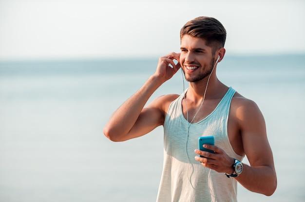 Ciesz się muzyką i świeżym powietrzem. szczęśliwy młody muskularny mężczyzna w słuchawkach, trzymając smartfon i uśmiechając się stojąc na zewnątrz outdoor