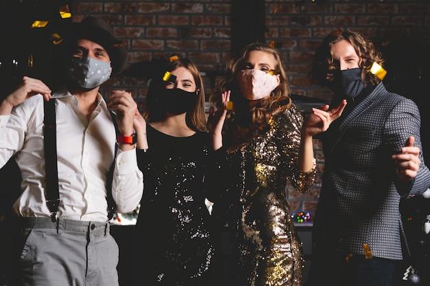 Ciesz się niesamowitą imprezą. koronawirus pandemia. grupa pięknych młodych ludzi w ochronnej masce medycznej tańczy, wygląda na szczęśliwą