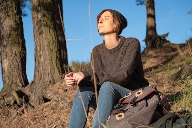 Ciesz się piękną jesienną pogodą na świeżym powietrzu. młoda kobieta turysta z zamkniętymi oczami siedzi pod sosnami w słoneczne popołudnie