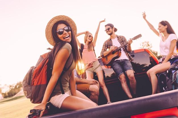 Ciesz się podróżą z najlepszymi przyjaciółmi. grupa młodych wesołych ludzi tańczących i grających na gitarze podczas wspólnej podróży samochodem pick-up