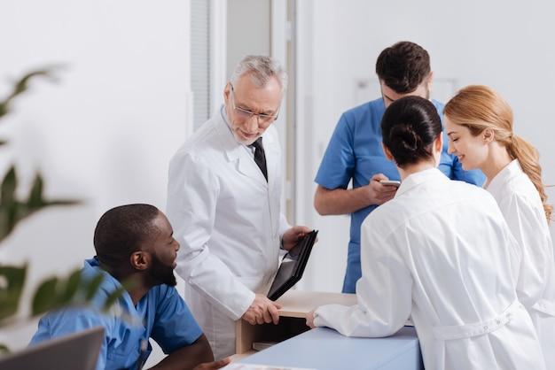 Ciesz się poranną rutyną w pracy. żywiołowo pozytywnie zaangażowani lekarze spotykają się rano w klinice i dzielą się wiadomościami z radością