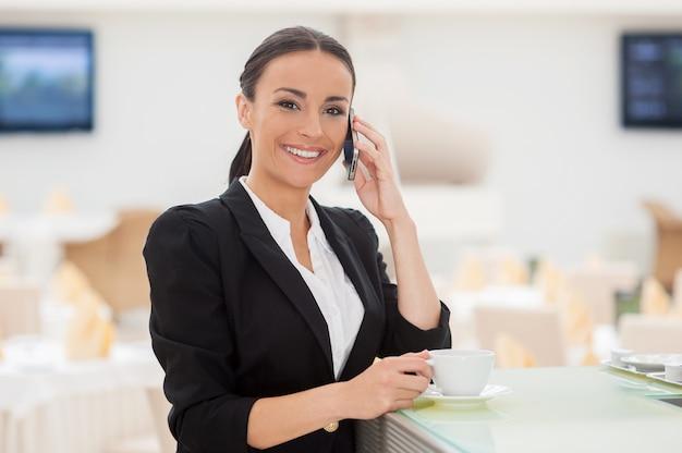 Ciesz się przerwą. piękna młoda kobieta w stroju formalnym pije kawę i rozmawia przez telefon komórkowy, opierając się o kontuar barowy