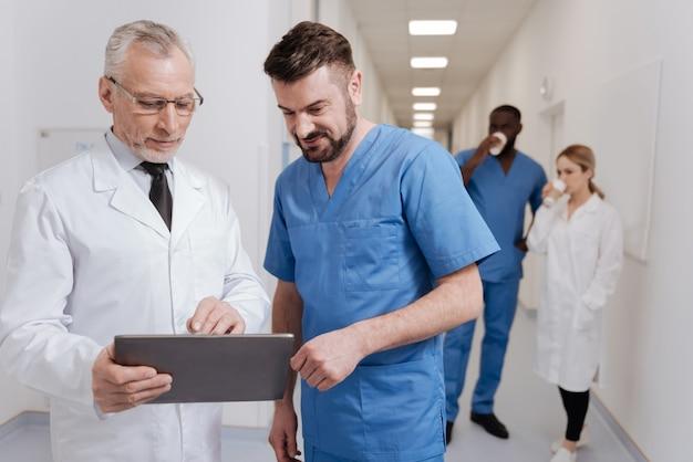 Ciesz się różnicą między pokoleniami. radośni, inteligentni, wyluzowani pediatrzy cieszą się pracą w szpitalu i pracą z tabletem, podczas gdy inni koledzy mają w tle przerwę na kawę