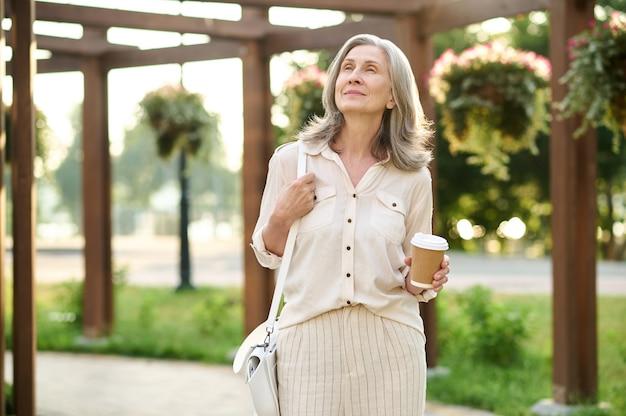Ciesz się spacerem. zamyślona kobieta w wieku emerytalnym z kawą patrząca pozytywnie na spacer po pięknym parku