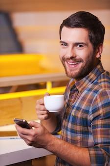 Ciesz się świeżo parzoną kawą. wesoły młody człowiek trzyma telefon komórkowy i pije kawę siedząc w kawiarni