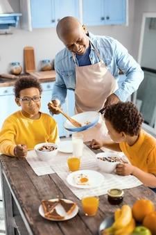 Ciesz się tym. wesoły młody człowiek serwujący swoim małym synom omlet i uśmiechający się czule, kiedy jedzą płatki śniadaniowe