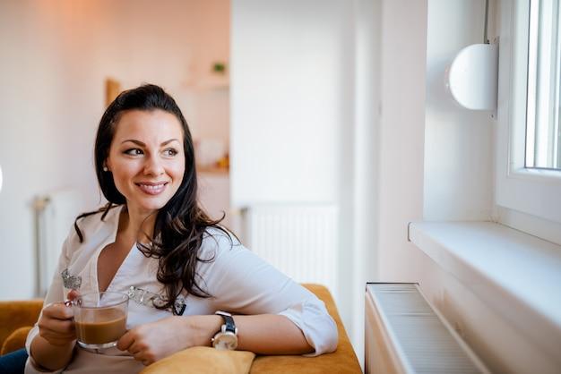 Ciesz się wolnym czasem w domu. wspaniała kobieta patrzeje przez okno i pije kawę w domu.