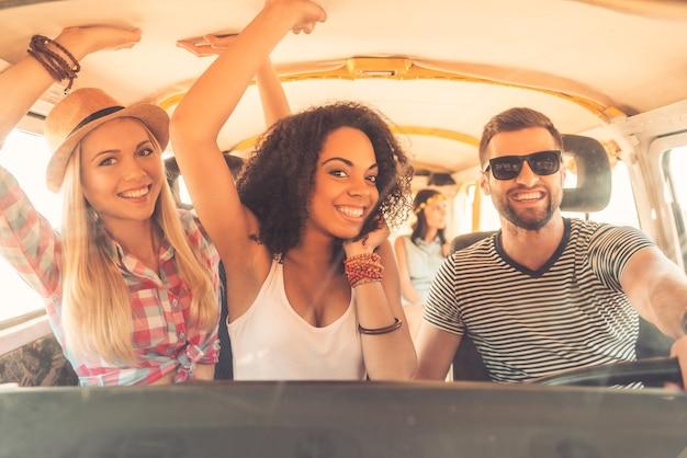 Ciesz się wspaniałą podróżą z przyjaciółmi. grupa wesołych młodych ludzi bawiących się siedząc wewnątrz minivana