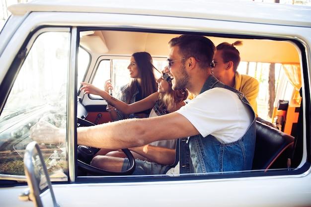 Ciesz się wspaniałą wycieczką z przyjaciółmi. grupa wesołych młodych ludzi, bawiąc się siedząc wewnątrz minivana.