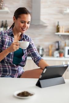 Ciesząc się filiżanką zielonej herbaty podczas korzystania z komputera typu tablet w kuchni