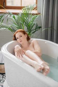 Ciesząc się kąpielą. całkiem naga kobieta cieszy się kąpielą i wygląda na zadowoloną