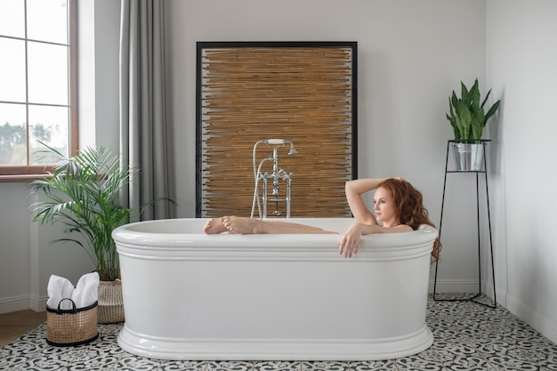 Ciesząc się kąpielą. ładna ruda kobieta leżąca w wannie i wyglądająca na zrelaksowaną